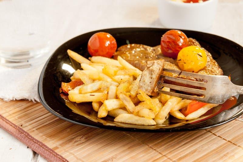 从seitan素食主义者的肉,西红柿和油炸物的素食牛排 免版税库存图片