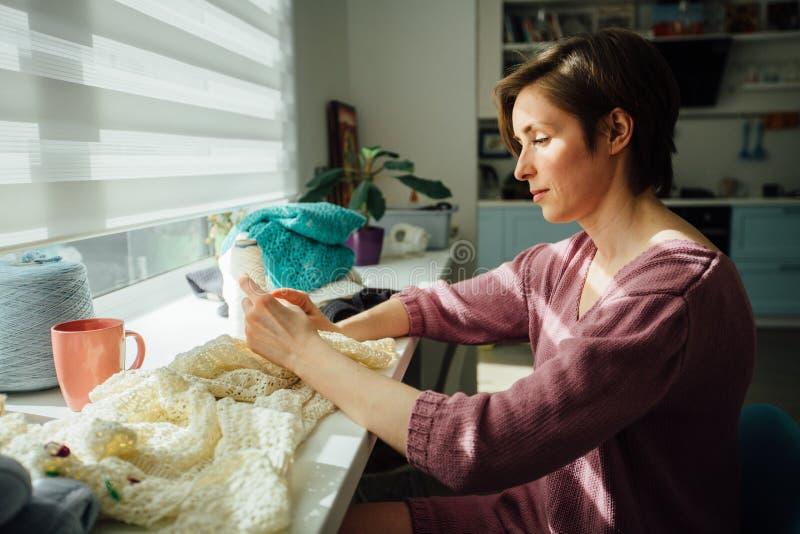 Seite der Frau zartes Kleid mit Häkelarbeit strickend Kreatives Arbeiten des weiblichen Freiberuflers am gemütlichen Hauptarbeits stockfotografie