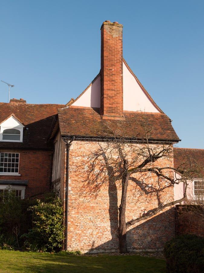 Seite des Hauses mit kleinem braunem bloßem Baum außerhalb des Gartens lizenzfreies stockfoto