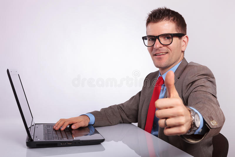 Seite des jungen Geschäftsmannes am Laptop, Daumen zeigend stockbilder