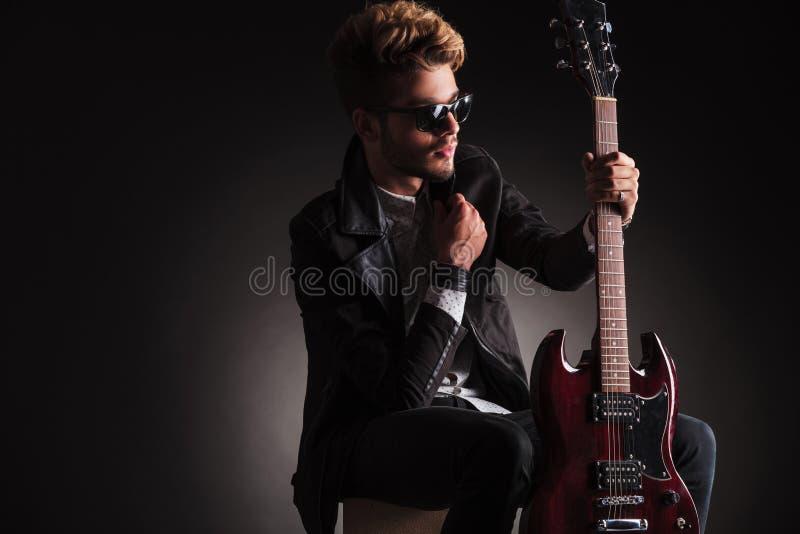 Seite eines kühlen Gitarristen, der seine Gitarre sitzt und hält lizenzfreie stockfotos