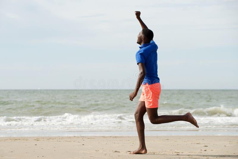 Seite in voller Länge des glücklichen jungen Mannes, der am Strand mit den Armen angehoben läuft stockbild