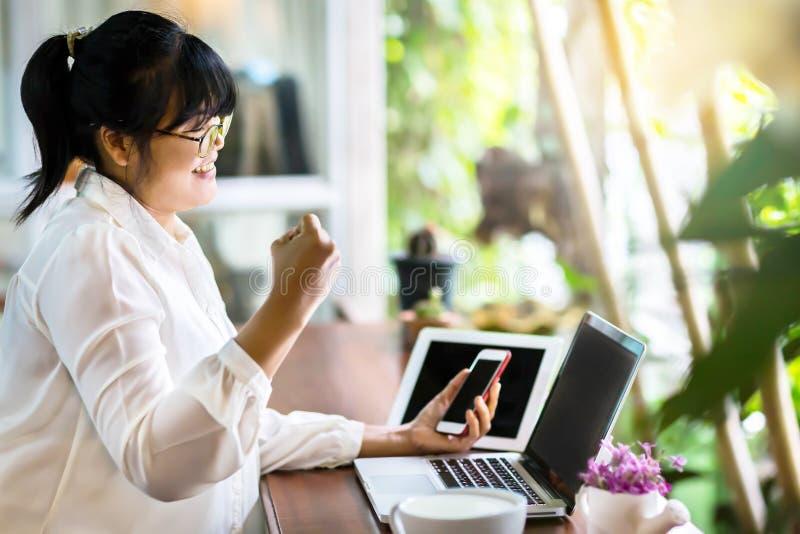 Seitenansicht der asiatischen Geschäftsfrau sitzend am langen Tisch in der Kaffeestube und Laptop-Computer und an den Showzeichen stockfotos