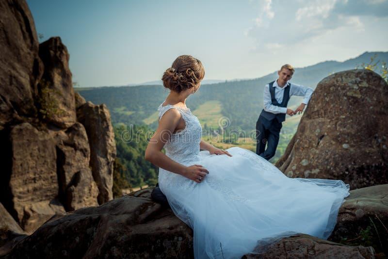 Seitenansicht der attractiuve elegent Braut, die auf dem Felsen sitzt und den unscharfen Bräutigam sich lehnt auf dem Felsen betr stockfotografie