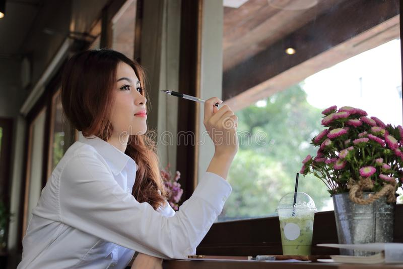 Seitenansicht der attraktiven jungen asiatischen Geschäftsfrau, die einen Stift hält und haben eine Idee im Kaffeecafé lizenzfreie stockfotos