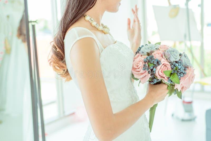 Seitenansicht der Braut hält einen Heiratsblumenstrauß und zeigt ihre Hochzeit stockfotografie