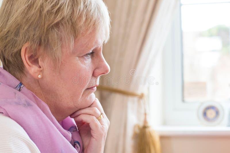 Seitenansicht der deprimierten älteren Frau zu Hause lizenzfreies stockbild