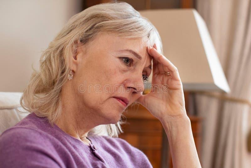 Seitenansicht der deprimierten älteren Frau zu Hause lizenzfreies stockfoto