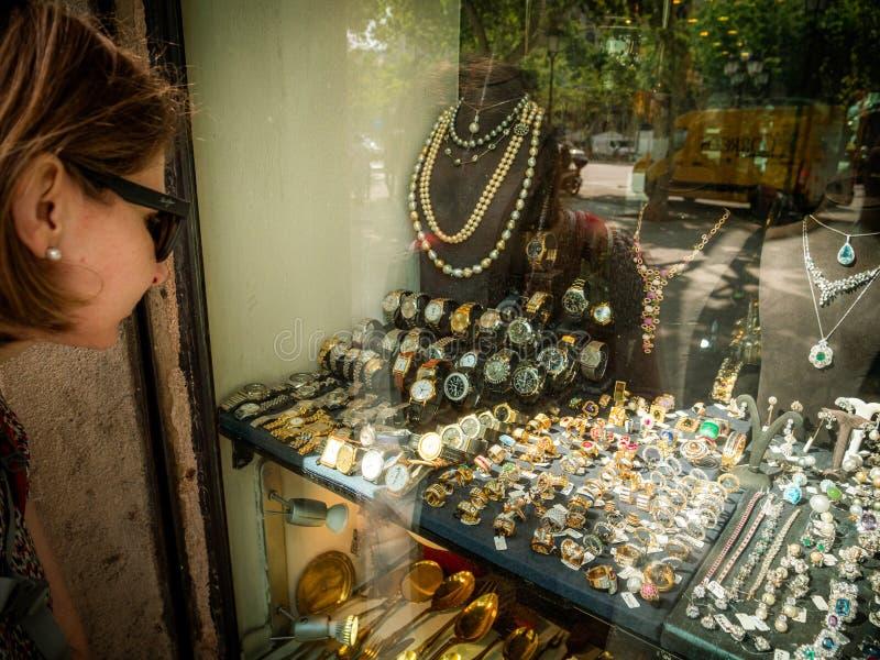 Seitenansicht der eleganten touristischen Frau, die das vordere Schaukastenfenster betrachtet stockfoto