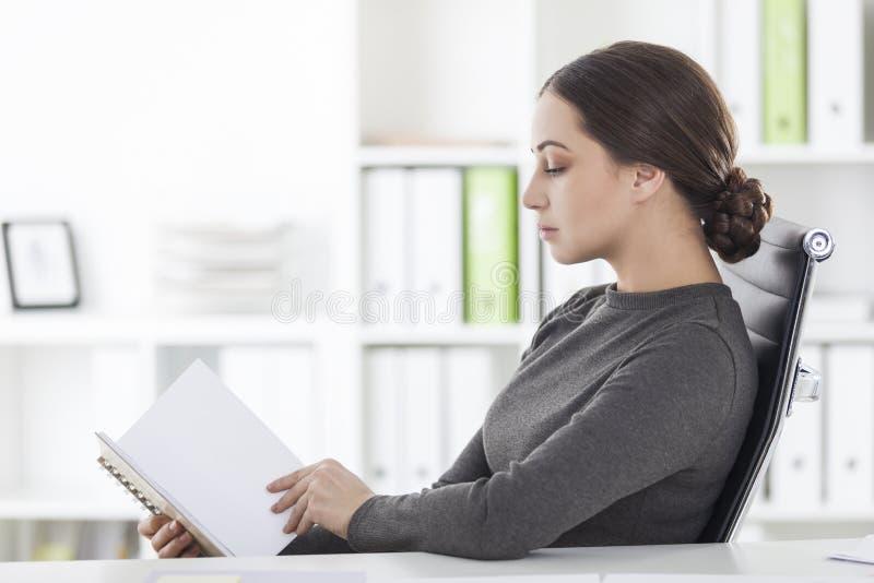 Seitenansicht der Frau in der grauen Lesung im Büro stockbilder