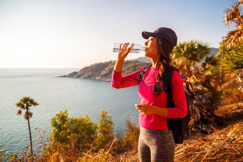 Seitenansicht der Frau mit Rucksack und einer Flasche Wasser Meer beim Sitzen betrachtend auf Hügel gegen Himmel lizenzfreies stockbild
