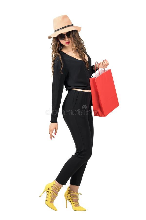 Seitenansicht der gehenden Frau mit der Einkaufstasche, die zurück unten schauen dreht lizenzfreie stockfotografie