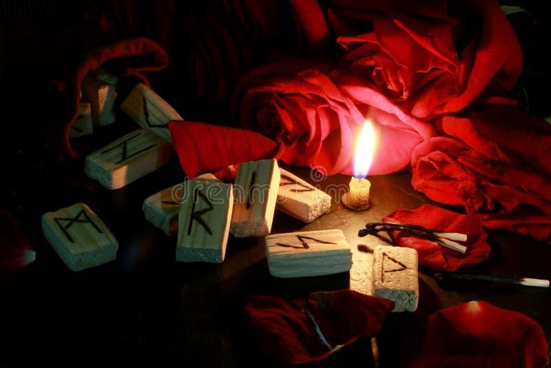 Seitenansicht der hölzernen Runen, sind herum die Blumenblätter von roten Rosen, eine Kerze brennt folgend Hinter den Kerzen sind stockbilder