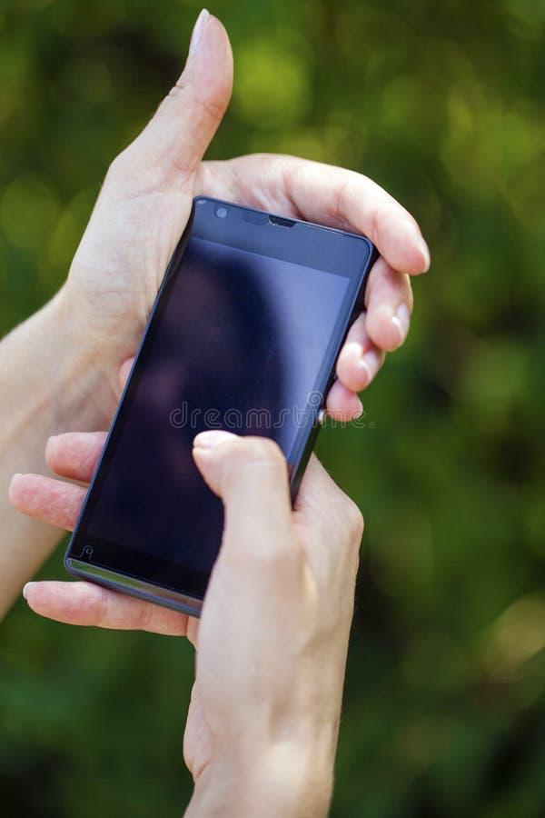 Seitenansicht der Hand einer Frau, die einen modernen glatten Smartphone hält stockfotos