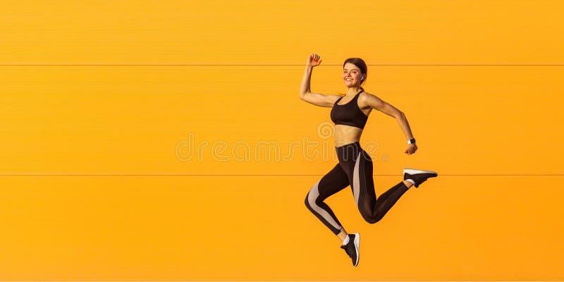 Seitenansicht der jungen erfüllten attraktiven sportlichen Frau im modernen schwarzen Sportkleidungsläufer herein auf orange Wand stockbilder