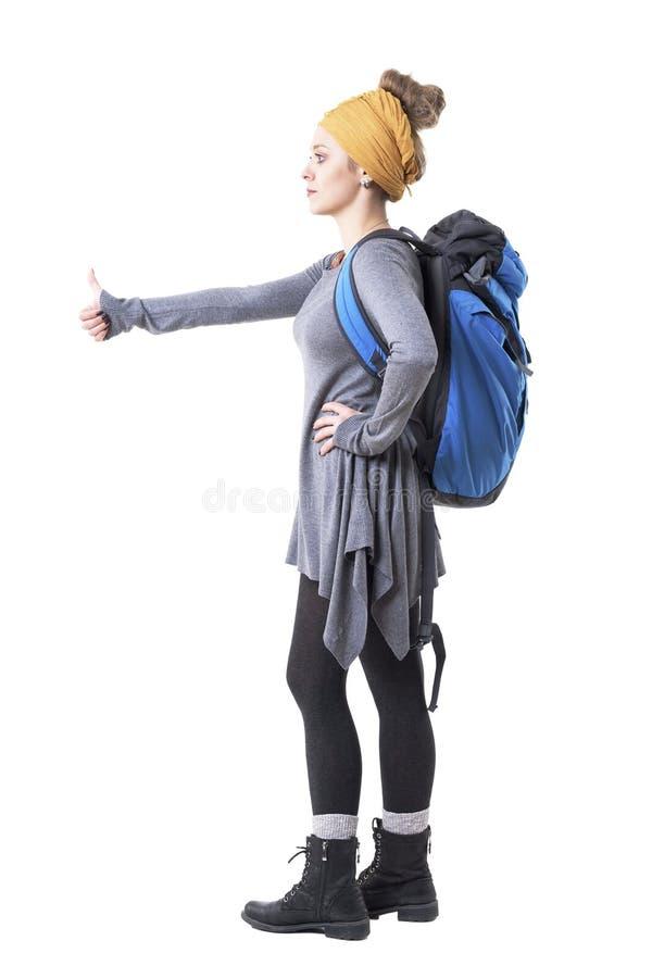 Seitenansicht der jungen Frau des kühlen stilvollen Hippies mit Rucksack weg per Anhalter fahrend und schauend lizenzfreies stockfoto