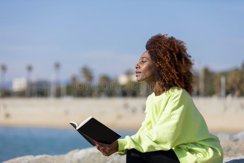 Seitenansicht der jungen gelockten Afrofrau, die auf einem Wellenbrecher h?lt ein Buch beim weg l?cheln und drau?en schauen sitzt lizenzfreie stockfotografie