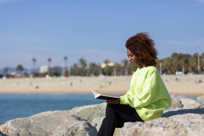 Seitenansicht der jungen gelockten Afrofrau, die auf einem Wellenbrecher h?lt ein Buch beim weg l?cheln und drau?en schauen sitzt stockfotografie