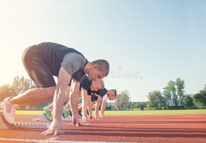 Seitenansicht der Nahaufnahme von den geernteten Leuten bereit, auf Bahnfeld zu laufen stockfotografie
