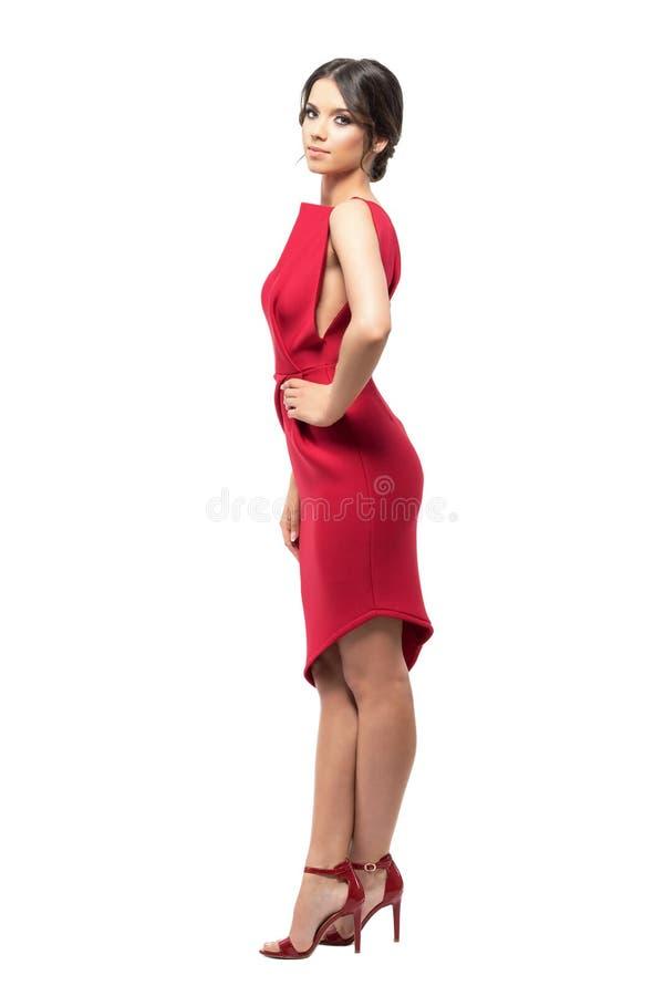 Seitenansicht der recht jungen lateinischen Frau im roten Kleid mit den Händen auf den Hüften, die Kamera betrachten stockfoto