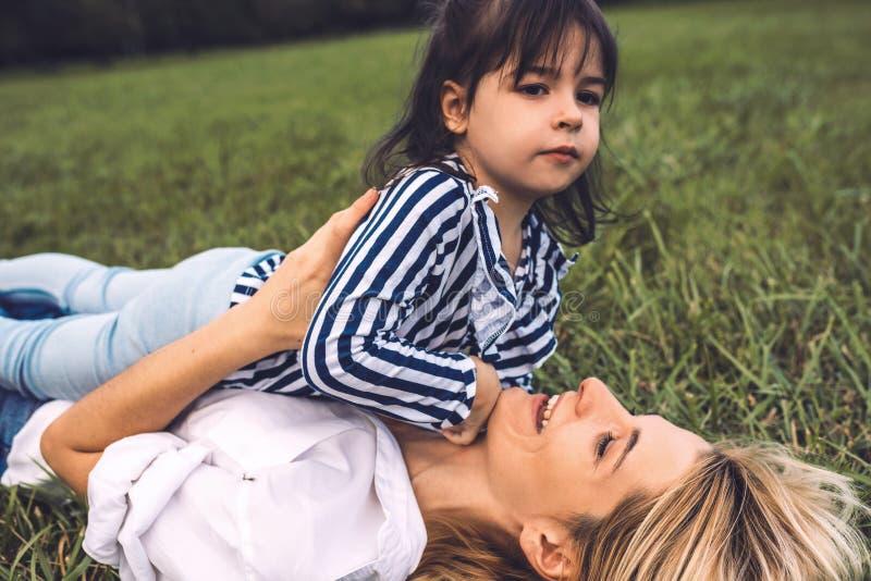 Seitenansicht der Schönheit mit ihrem netten wenig Mädchen auf dem grünen Gras spielend im Freien Liebende glückliche hübsche Mut stockfotos