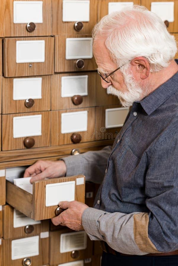 Seitenansicht des älterem männlichem Archivarsuchens lizenzfreies stockfoto