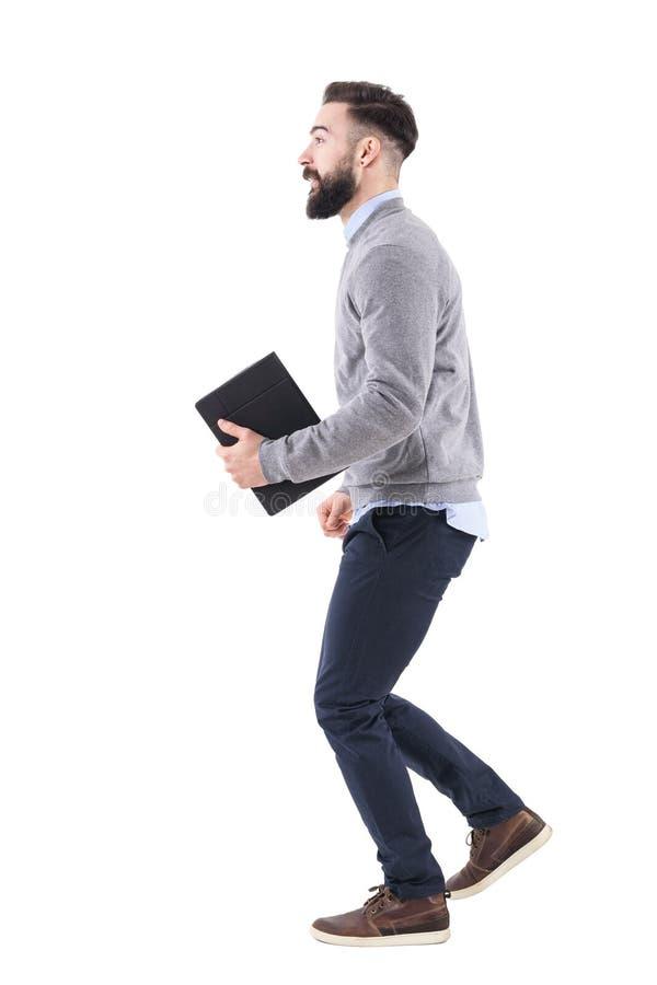 Seitenansicht des aufgeregten intelligenten zufälligen Geschäftsmannes, der in der Hand mit Notizbuch läuft lizenzfreies stockbild