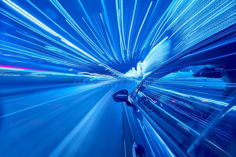 Seitenansicht des Autos bewegend in eine Nachtstadt stockfotografie