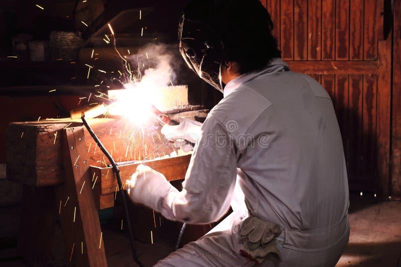 Seitenansicht des Berufsschweißers im Arbeitskleidungsschweißensstahl mit Funken in der Werkstatt Industrielles Konzept stockfoto
