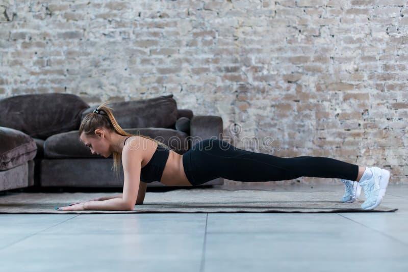 Seitenansicht des dünnen weiblichen Athleten, der in Plankenposition auf dem Boden verstärkt Kern steht, mischt zuhause mit lizenzfreie stockbilder