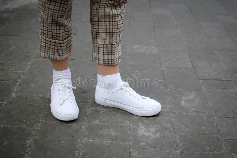 Seitenansicht des Fußes der jungen Frauen in den weißen Turnschuhen auf Asphalthintergrund lizenzfreies stockfoto