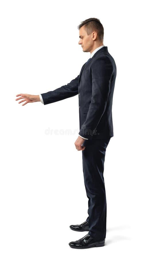 Seitenansicht des Geschäftsmannes erreicht heraus, um etwas zu öffnen, lokalisiert auf weißem Hintergrund lizenzfreie stockfotos
