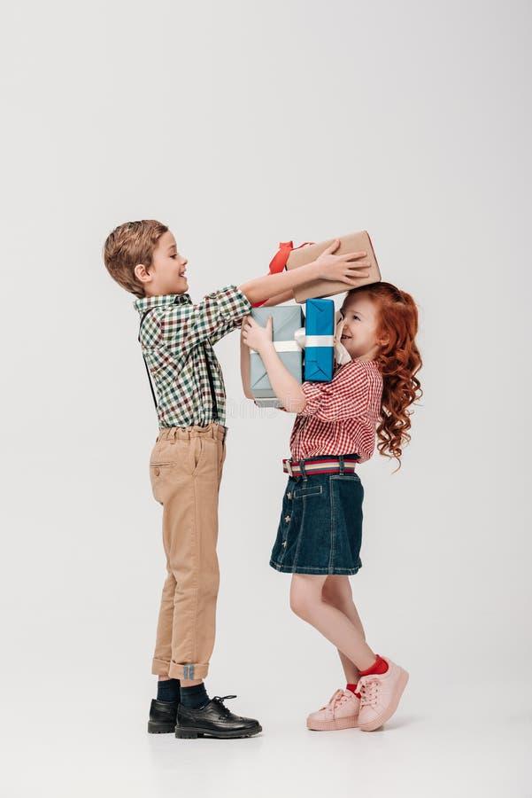 Seitenansicht des glücklichen Jungen Geschenkboxen lächelndem kleinem Mädchen darstellend lizenzfreie stockbilder