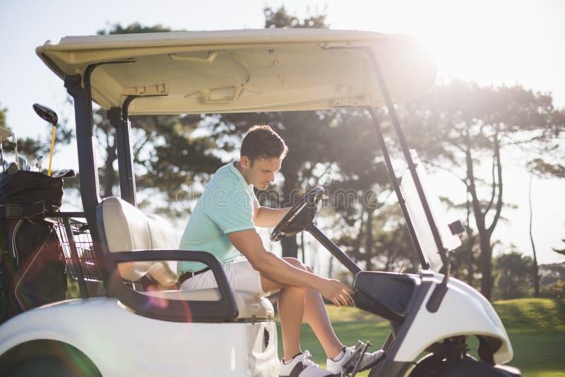 Seitenansicht des Golfspielermannes sitzend im Golfbuggy lizenzfreie stockbilder