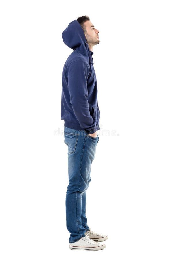 Seitenansicht des hübschen überzeugten kühlen jungen Kerls mit Hoodie auf dem Kopf, der oben schaut lizenzfreie stockfotografie