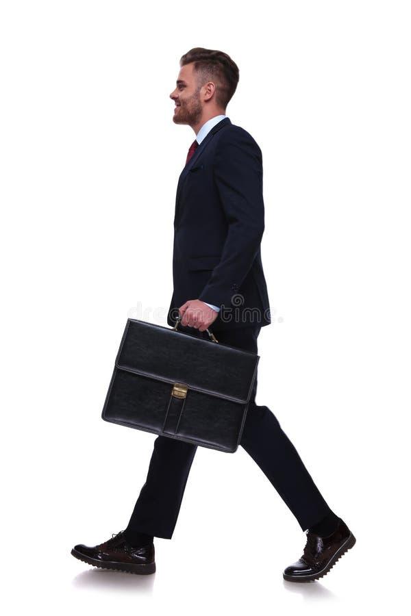 Seitenansicht des hübschen jungen Geschäftsmannes, der arbeiten geht stockfotografie