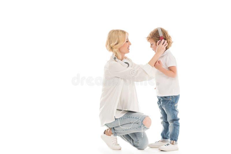 Seitenansicht des helfenden Sohns der Mutter, zum von Kopfhörern an zu setzen lizenzfreies stockfoto