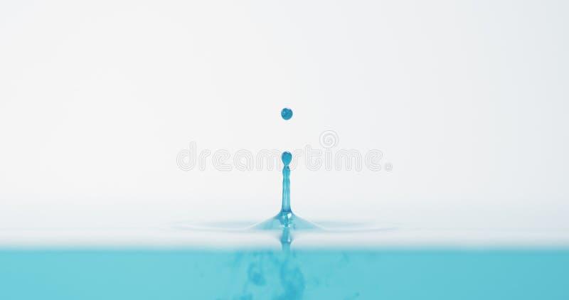 Seitenansicht des hellen Tropfens des blauen Wassers mit genauem Spritzen stockbilder