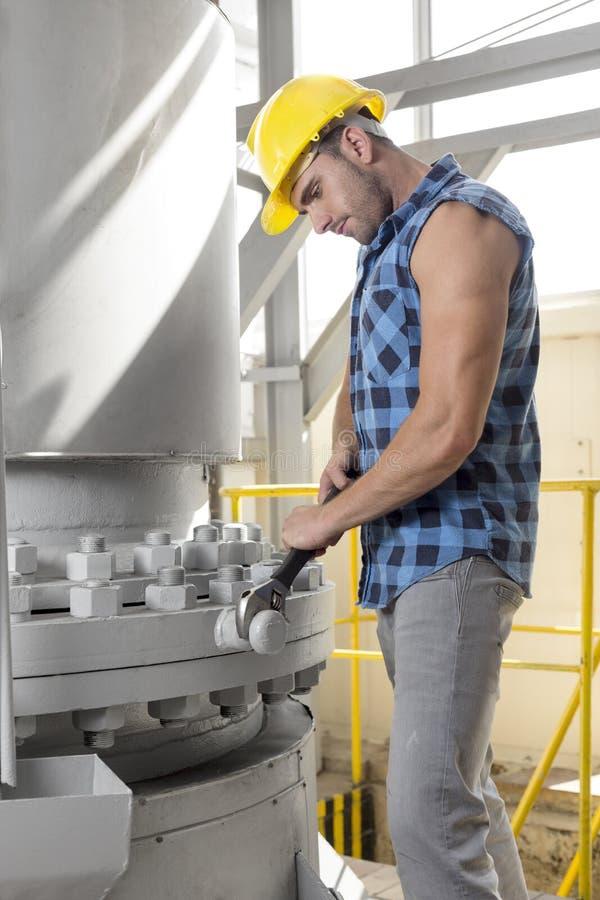 Seitenansicht des jungen Arbeiters, der Schlüssel auf industrieller Maschine verwendet stockfotografie