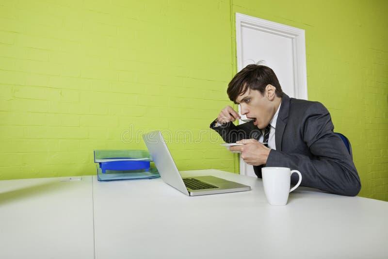 Seitenansicht des jungen Geschäftsmannes essend bei Laptop bei Tisch verwenden lizenzfreies stockbild