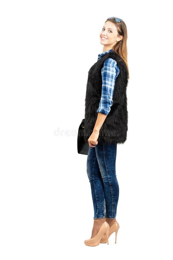 Seitenansicht des jungen glücklichen zufälligen Mode-Modells, das an der Kamera lächelt lizenzfreie stockbilder
