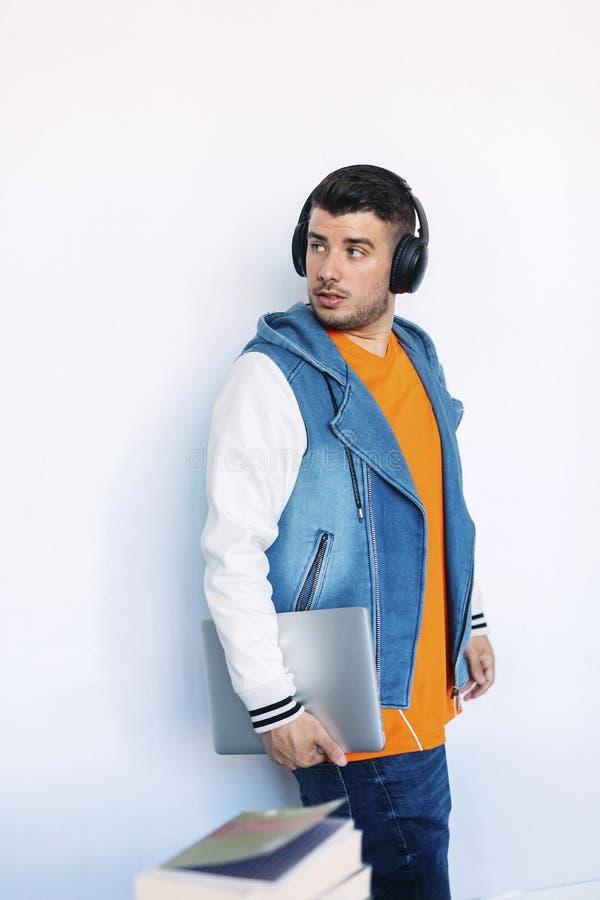Seitenansicht des jungen Mannes in der zuf?lligen stehenden Kleidung beim weg schauen und Tragen eines Tabletten-PC lizenzfreie stockbilder