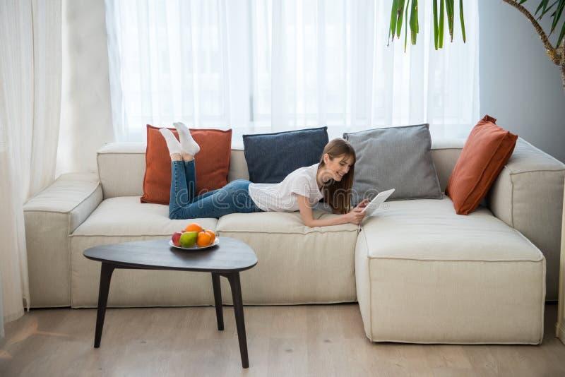 Seitenansicht des jungen weiblichen Lügens auf Couch und der Anwendung der digitalen Tablette im Wohnzimmer stockbild