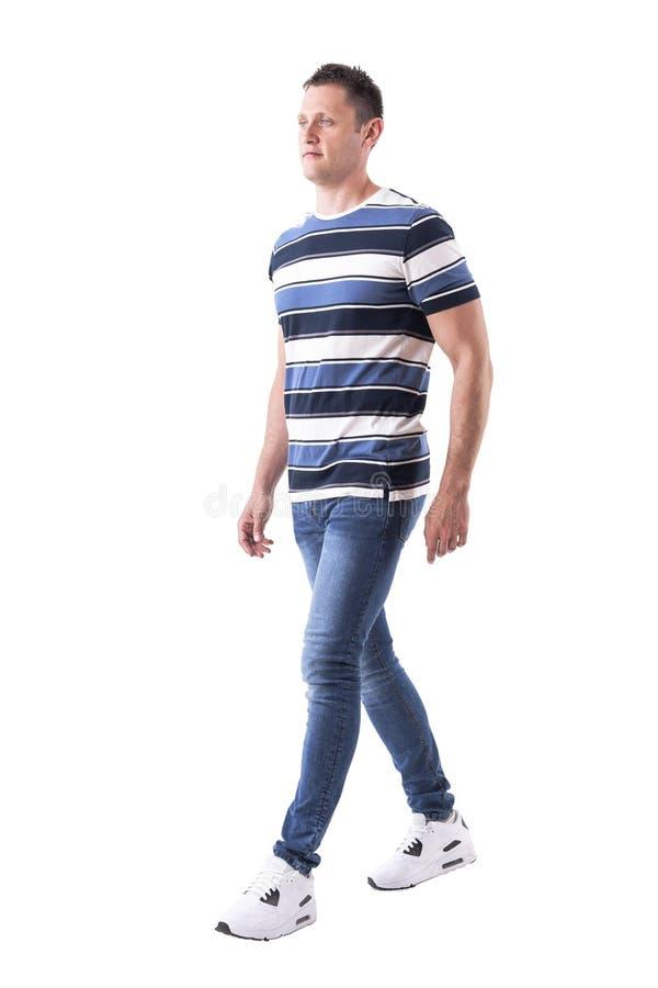 Seitenansicht des kühlen hübschen erfolgreichen Mannes, der weg in der zufälligen Kleidung geht und schaut stockfotografie