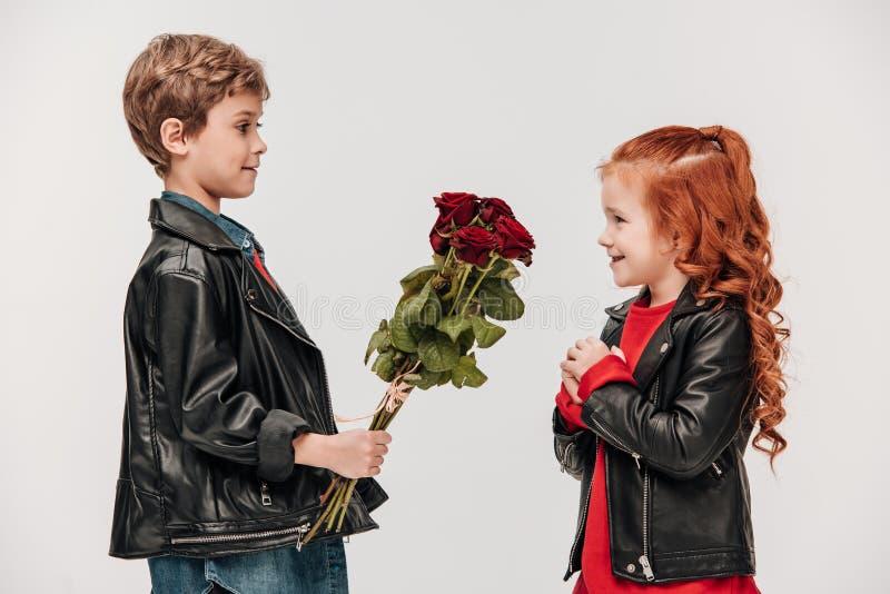 Seitenansicht des kleinen Jungen Rosen Blumenstrauß seiner Freundin darstellend lizenzfreies stockfoto