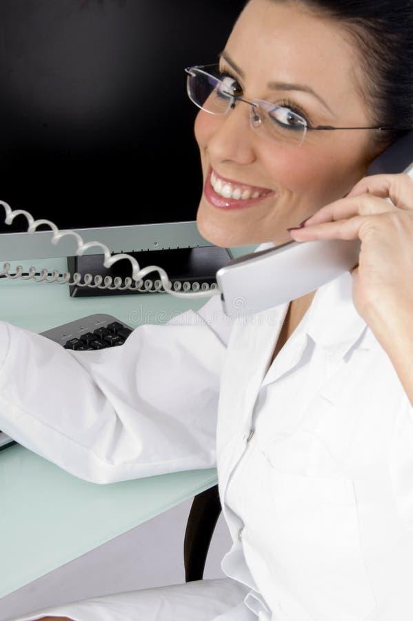 Seitenansicht des lächelnden Doktors sprechend am Telefon stockfotografie
