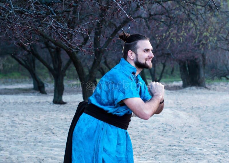 Seitenansicht des Lachens des hübschen bärtigen Mannes in der blauen Kimonostellung mit den umklammerten Händen stockfotografie