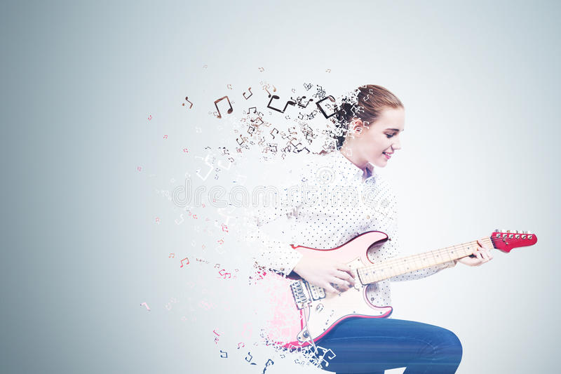 Seitenansicht des Mädchens E-Gitarre, Laubsäge spielend lizenzfreie stockfotos