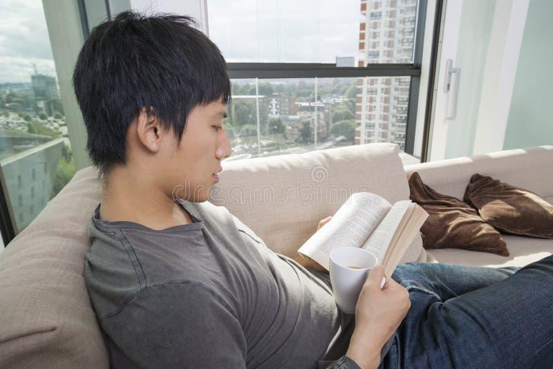 Seitenansicht des mittleren erwachsenen Mannes, der Kaffee während Lesebuch auf Sofa trinkt lizenzfreies stockbild