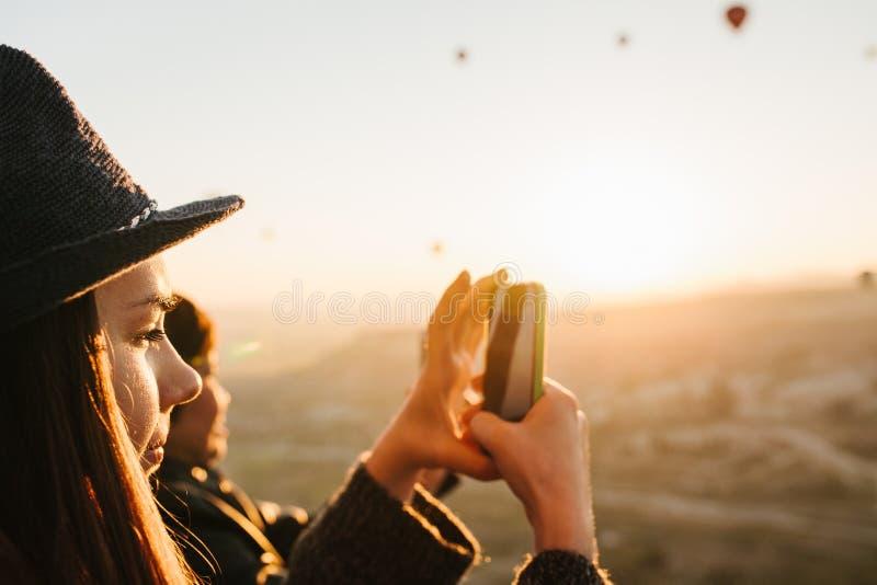 Seitenansicht des reizend Brunettemädchens im Hut macht Foto auf Smartphone während der Flüge von vielen Heißluftballonen an stockfotos